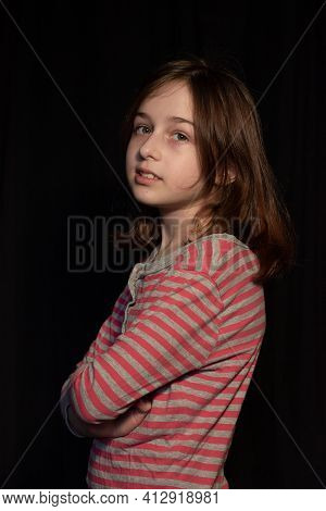 Young Beautiful Girl In A Pajamas On Black Background. Portrait Of A Girl In Pink Striped Pajamas