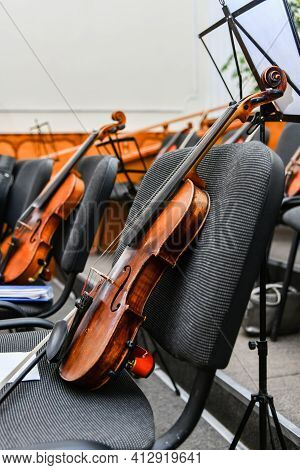 Violins Stand On Empty Chairs Of The Concert Hall Before The Start Of The Symphony Concert.