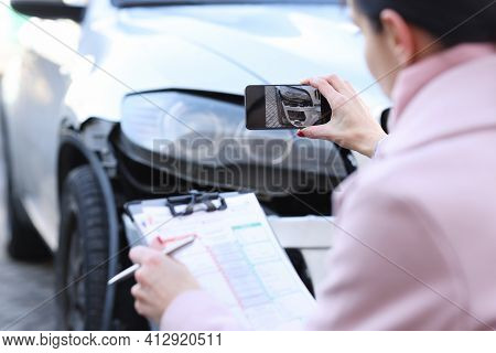 Insurance Agent Taking Pictures Of Wrecked Car Closeup