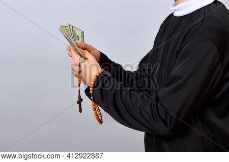A Young Catholic Pastor Counts Dollars After The Service. Corruption In Christianity And Catholicism