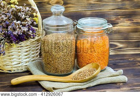 Buckwheat And Lentils In A Glass Jar On A Wooden Background, Rustic Authentic Style. Copy Space. Die