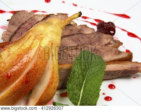 Sliced Roasted Duck Fillet With Pear And Berry Sauce On White Round Plate. Close Up Shot