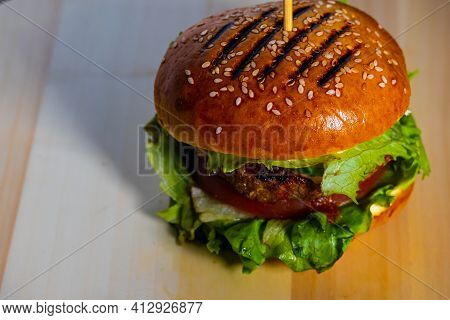 Juicy Tasty Meat Burger With Cheese, Herbs And Vegetables On A Wooden Tray, Ready To Eat.