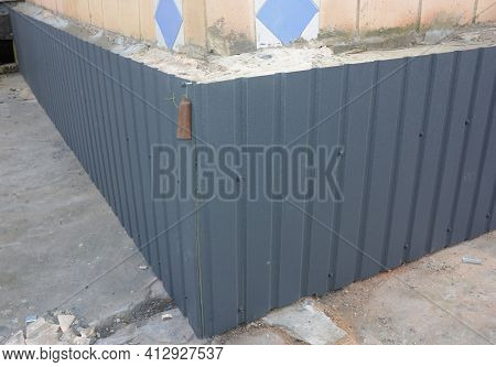 An Outside Old Brick Foundation Is Covered With Metal Siding, Steel Siding To Protect The Foundation