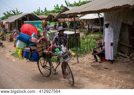 Zanzibar, Tanzania - January 2020: Black African Man With Bicycle Loaded With Good And Household Too