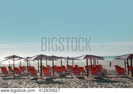 Red Umbrellas And Chaise Lounges On The Beach Of Atlantic Ocean In Espinho, Portugal