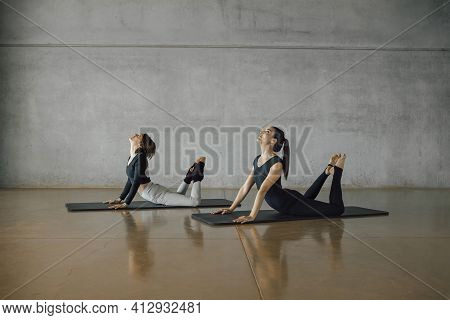 Brunette Female Coach Mentoring A Woman To Practice Pilates Stretching Exercise, Workout During Pers