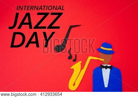 World Jazz Day. Silhouette Of A Musician With A Saxophone From Which Melodies Flew Out, On A Red Bac