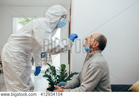 Health Professional In Ppe Suit And Face Shield Introducing A Nasal Swab To A Senior Adult Patient A
