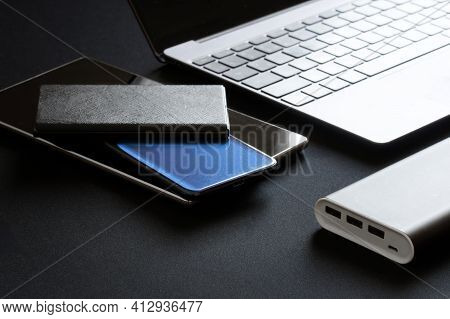 The External Battery - Power Bank Lies Next To Many Gadgets: A Tablet, Two Smartphones And A Laptop