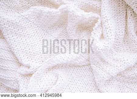 Warm Knitted Blanket Of White Color Close-up.the Blanket Lies In Uneven Waves. Winter Or Autumn Back