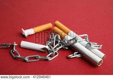 Cigarettes And Chain On Red Background. Quitting Smoking Concept