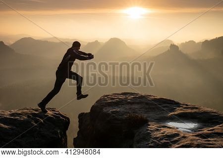 Strong Mountain Climber Hiking And Jumping Over  The Summit Ridge Of A Peaks At Sunset. Man Takes Le
