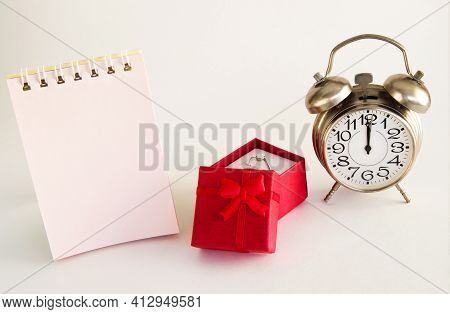 Red Box Of Special Gifts With A Ring And A Clock On A Light Background With A Place For An Inscripti