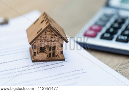 A Model Wooden House Placed On The House Purchase Contract Real Estate Ideas, Buying A Home, Landlor