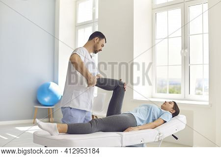 Young Man Osteopath Checking Joints Of Lying Woman Patients Legs