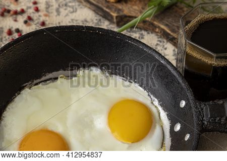 Fried Eggs In The Iron Pan And Cup Of Coffee For Breakfast