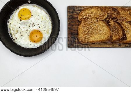 Fried Eggs With Parsley In A Rustic Iron Pan, Toast On A Wooden Board And A Cup Of Coffee For Breakf