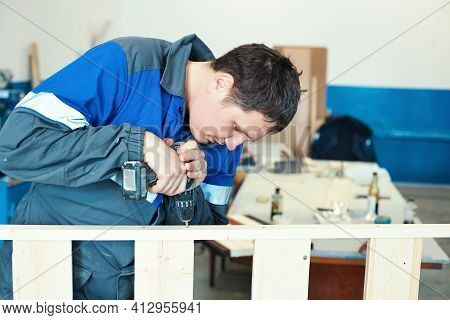 A Young Worker In Overalls With A Screwdriver Collects Furniture In A Carpenters Shop. A White Man S