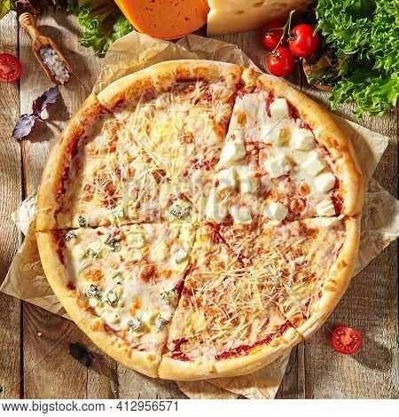Four Cheese Pizza or Quattro Formaggi Pizza topped with tomato sauce, mozzarella, gorgonzola, Parmigiano Reggiano, and goat cheese. Rustic style pizza layout.