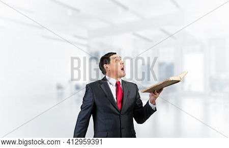 Surprised Businessman Holding Open Book And Looking Up. Startled Adult Man In Business Suit And Tie
