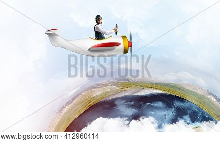 Aviator In Leather Helmet Driving Small Propeller Plane In Cloudy Blue Sky. Extreme Aviation Hobby A