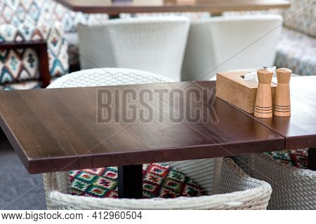 Wooden Napkin Holder With Salt And Pepper Shaker On A Wooden Table Of A Summer Terrace Of A Restaura