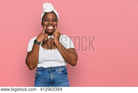 Young african woman with turban wearing hair turban over isolated background smiling with open mouth, fingers pointing and forcing cheerful smile