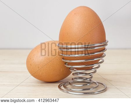 Fresh boiled eggs in egg cup for breakfast on wooden table at kitchen.