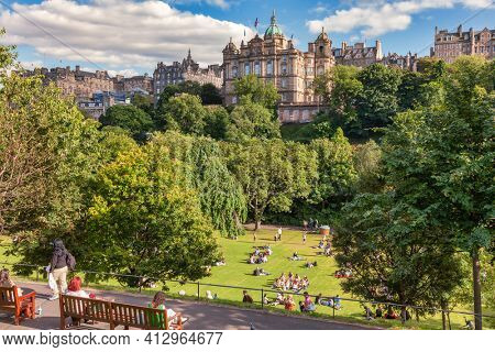Edinburgh, UK - Aug 9, 2012: Locals and tourists enjoy warm sunny summer day relaxing and picnicking at the Princes Street Gardens, a famous public park in the city center