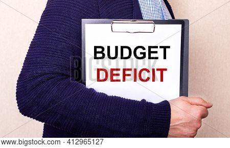Budget Deficit Is Written On A White Sheet Held By A Man Standing Sideways