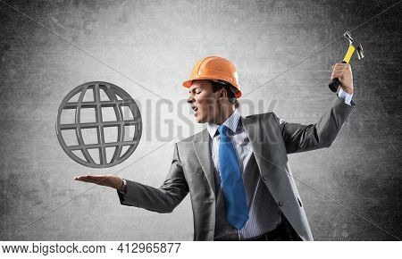 Furious Businessman Going To Crash Earth 3d Symbol With Hammer. Young Handsome Man In Business Suit