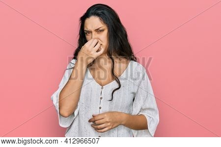Brunette young woman wearing casual clothes smelling something stinky and disgusting, intolerable smell, holding breath with fingers on nose. bad smell