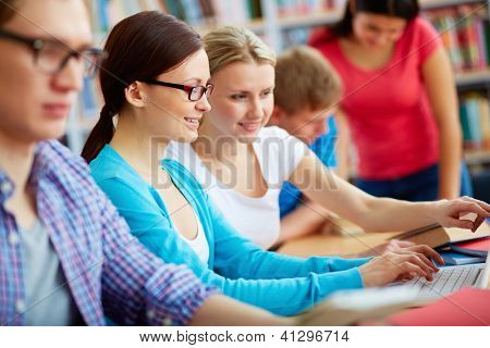 Portrait of pretty girl typing on laptop with her group mate pointing at its screen at lesson