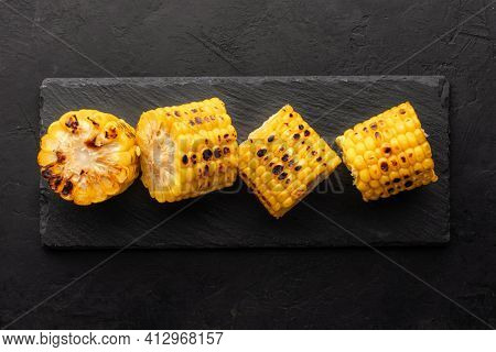 Grilled corn on a slate board, top view, rustic black background.