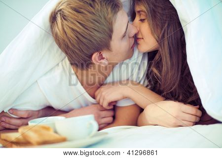 Young amorous couple kissing under blanket