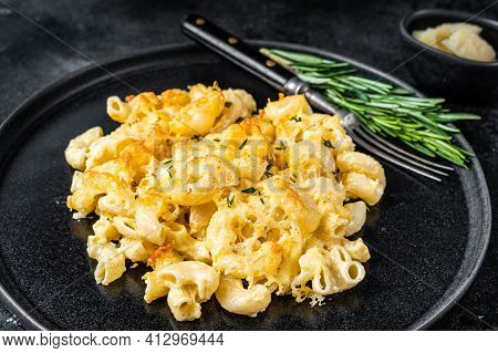 Baked Macaroni Mac And Cheese American Dish With Cheddar Cheese Sauce. Black Background. Top View