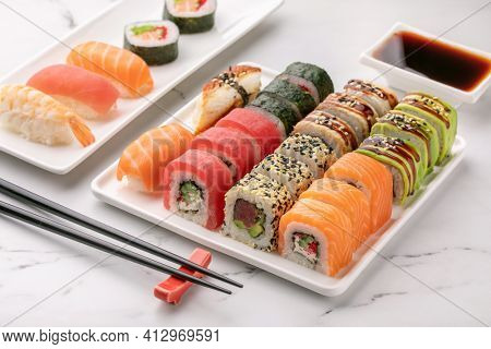 Various sushi rolls, soya sauce and chopsticks on a white stone background. Traditional Japanese food. Asian food