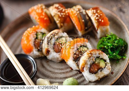 Sushi maki rolls with salmon, eel, avocado, cucumber on a plate with chopsticks, soy sauce, wasabi and ginger. Japanese traditional fish food closeup served for lunch in modern gourmet restaurant