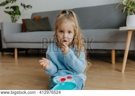 Little Girl Paints Her Lips With Baby Lipstick. Cute Kid Makes Makeup With Toy Cosmetics At Home. Co