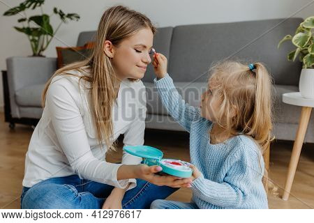 Little Daughter Makes Makeup To Mother With Toy Cosmetics. Kid Playing On Beauty Game With Mother At