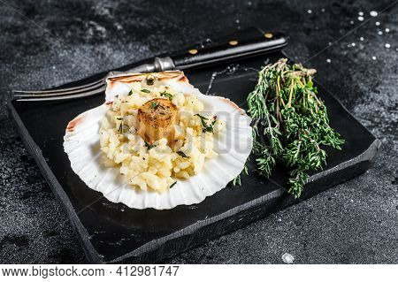 Risotto With Pan Seared Sea Scallops In A Shell. Black Background. Top View