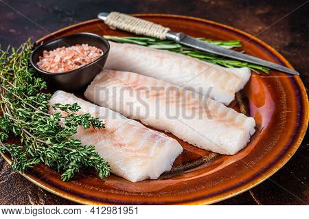 Raw Cod Loin Fillet Steaks On Rustic Plate With Thyme And Salt. Dark Background. Top View