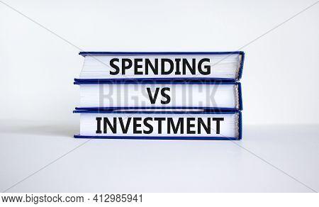 Spending Vs Investment Strategy Symbol. Books With Words 'spending Vs Investment'. Beautiful White B