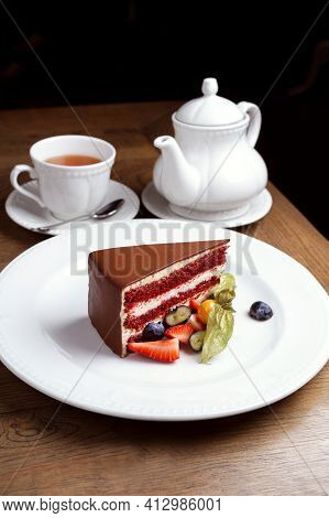 Chocolate Dessert With Strawberries, Blueberries, Physalis. White Dishes,сup Of Black Tea. Tea Drink
