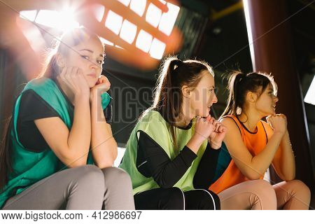 A Team Of Young Girls Sitting On The Bench In Multi-colored Vests Are Worried And Worried About Thei