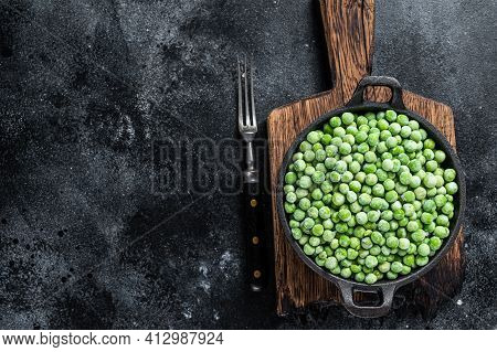 Fresh Frozen Green Peas In A Pan. Black Background. Top View. Copy Space