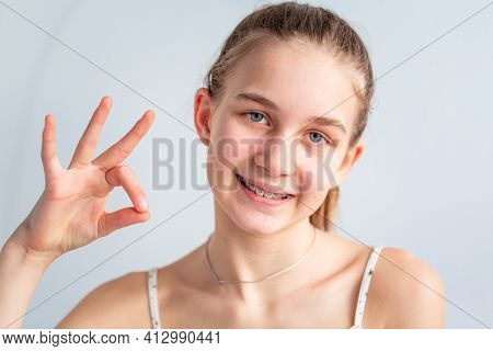 Teenage Girl Smiling In Orthodontic Brackets Showing Ok Sign. Girl With Braces On Teeth.