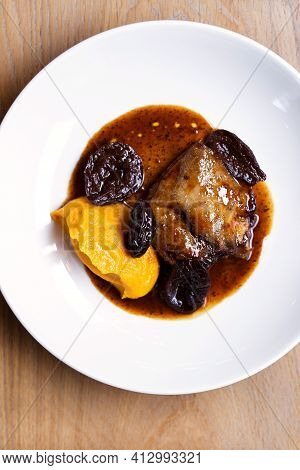 Meat With Prunes And Pumpkin Puree In Sauce, In A White Plate. Flat Lay. Vertical Photo