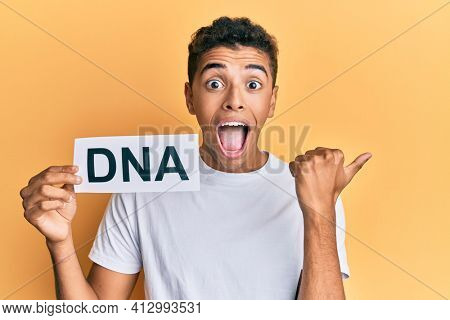 Young handsome african american man holding dna word pointing thumb up to the side smiling happy with open mouth